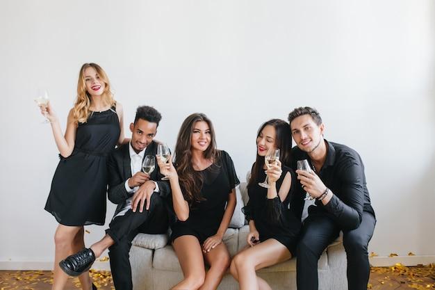 Retrato interno de jovens satisfeitos com taças de champanhe