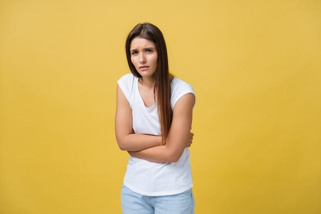 Retrato interno de linda garota em pé com as mãos cruzadas na barriga, sentindo-se estranho ou sofrendo de dor ao olhar para o lado, em pé contra um fundo amarelo. mulher tem dor de estômago.