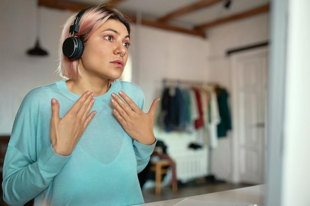 Retrato interno de linda jovem séria com cabelo rosado, posando em casa com fones de ouvido sem fio