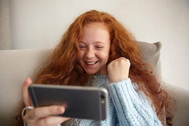Retrato interno de menina sorri e mostra o gesto de vitória enquanto joga seu videogame favorito em seu telefone.