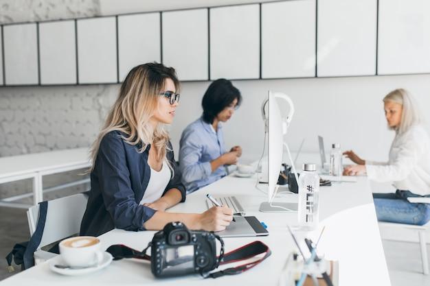 Retrato interno de meninas europeias trabalhando em um projeto com um colega asiático no escritório e conversando