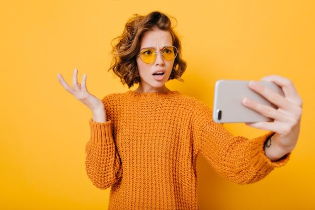Retrato interno de mulher decepcionada de cabelo curto de óculos fazendo selfie no estúdio