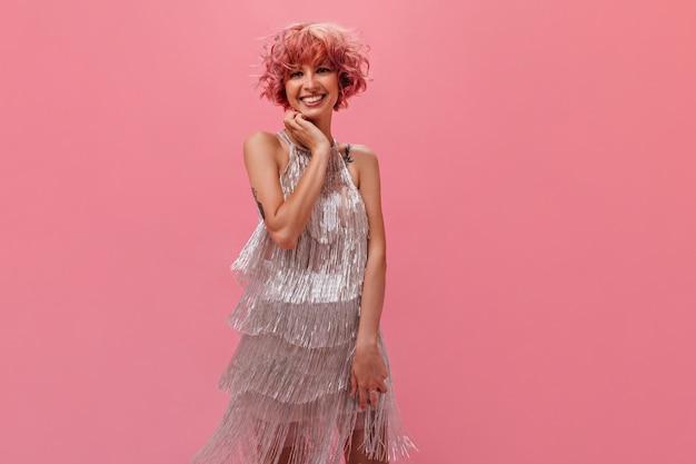 Retrato interno de mulher feliz encaracolada em vestido festivo prateado sorrindo sinceramente isolado