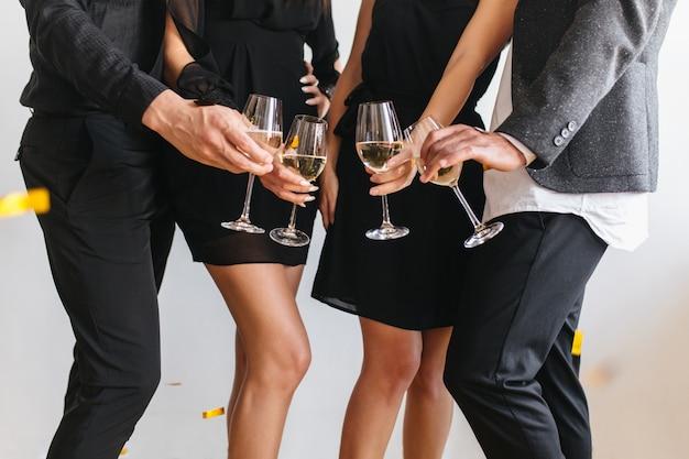 Retrato interno de pessoas tilintando óculos com caras em trajes pretos