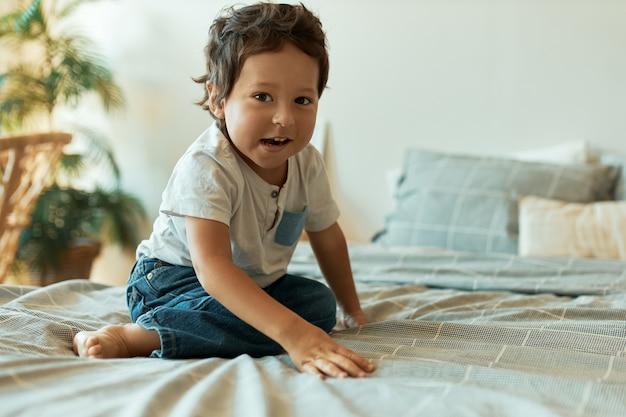 Retrato interno de um adorável bebê com pele escura, cabelo encaracolado e pés descalços, sentado na cama usando camiseta e jeans