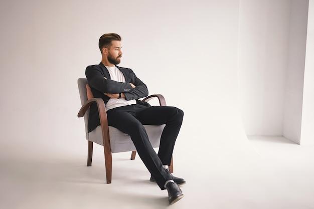 Retrato interno de um belo jovem advogado com barba espessa e penteado moderno, sentado confortavelmente na poltrona, com os braços cruzados sobre o peito e olhando para longe com expressão pensativa e pensativa