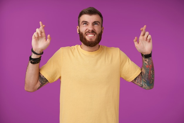 Retrato interno de um jovem barbudo com tatuagens e corte de cabelo da moda, franzindo a testa e olhando para cima, levantando as mãos com os indicadores cruzados, posando em roxo com roupas casuais