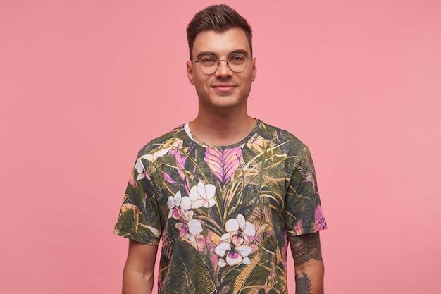 Retrato interno de um jovem bonito com tatuagens, usando óculos e camiseta florida, sorrindo gentilmente, isolado