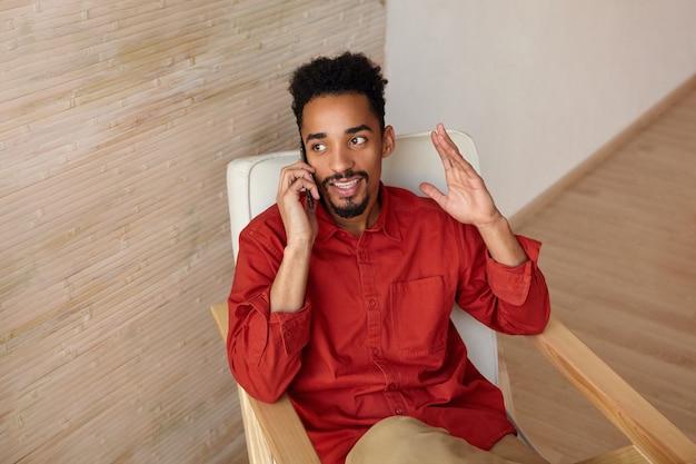 Retrato interno de um jovem bonito de cabelos curtos barbudo cara de pele escura, sentado na cadeira enquanto conversa por telefone e levanta emocionalmente a mão, posando no interior da casa