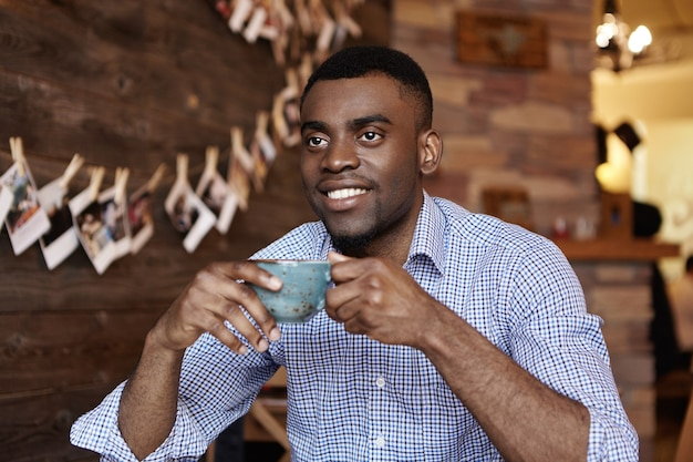 Retrato interno de um jovem empresário de pele escura ou trabalhador de escritório segurando uma xícara de café