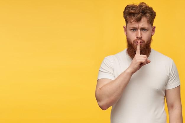 Retrato interno de um jovem ruivo caucasiano com uma barba ruiva grande e pesada, estrelando na frente, nervoso e mostra gesto de silêncio com um dedo