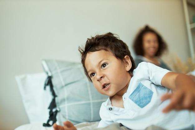 Retrato interno de um menino teimoso de 3 anos com pele escura, deitado na cama com a mãe, agindo de maneira travessa, não quer dormir