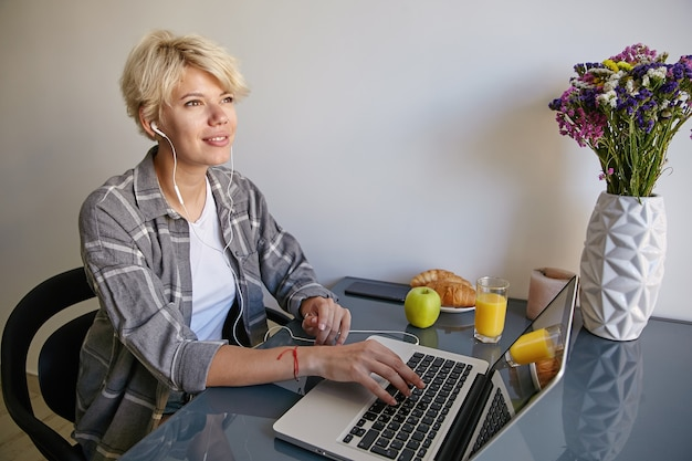 Retrato interno de uma adorável jovem com roupas casuais, sentada ao lado do laptop com fones de ouvido, segurando o teclado e sonhando com algo