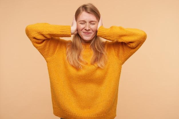 Retrato interno de uma adorável jovem de cabelos compridos com penteado casual, sorrindo levemente com os olhos fechados e segurando as orelhas das mãos levantadas, posando em bege