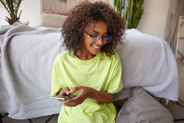 Retrato interno de uma adorável jovem mulher encaracolada usando óculos e camiseta amarela, olhando para longe com um sorriso encantador, segurando o celular nas mãos