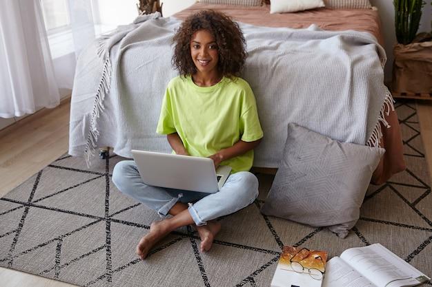 Retrato interno de uma encantadora mulher alegre com cabelo castanho cacheado sentada no tapete com estampa geométrica, segurando o laptop nas pernas e sorrindo