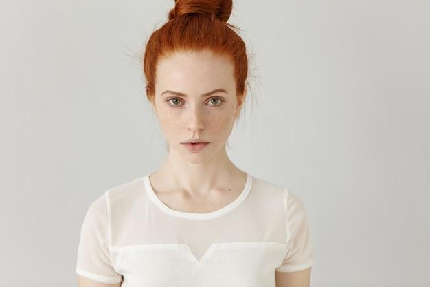 Retrato interno de uma garota ruiva bonita e atraente com coque e sardas