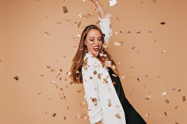 Retrato interno de uma jovem modelo feminina com cabelo castanho claro, vestindo jaqueta branca e vestido preto, dançando e se divertindo na parede bege com confete