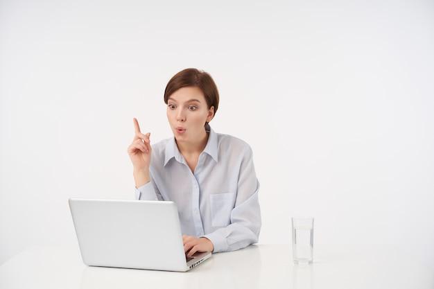 Retrato interno de uma jovem morena de cabelos curtos, contornando sua boca com entusiasmo e levantando o dedo indicador enquanto ela está tendo uma boa ideia, posando em branco