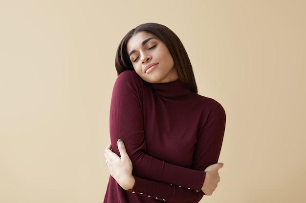 Retrato interno de uma jovem morena relaxada e positiva, fechando os olhos de prazer, mantendo os braços em volta de si mesma, desfrutando do tecido macio de seu novo suéter de cashmere marrom com gola alta