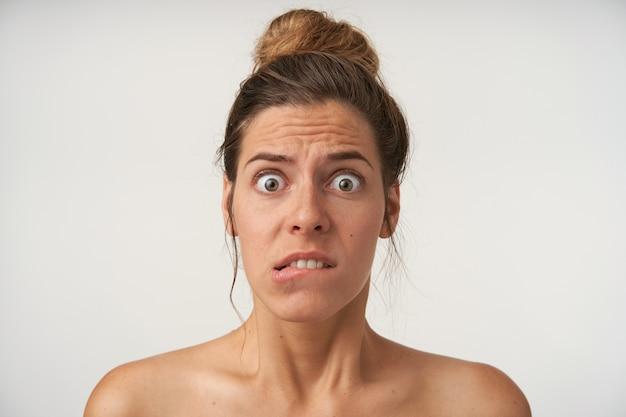 Retrato interno de uma jovem mulher assustada com penteado coque, testa enrugada e lábio inferior mordido com olhos arregalados