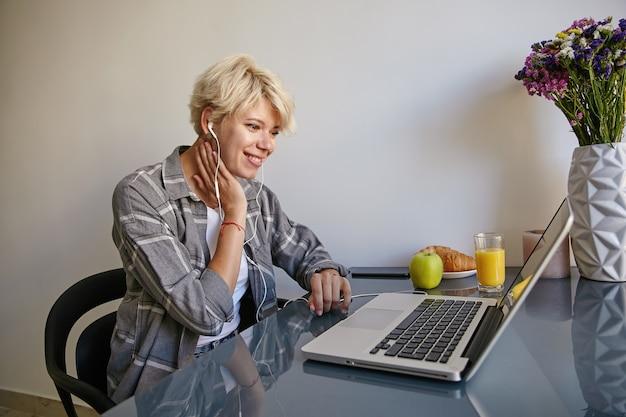 Retrato interno de uma jovem mulher com cabelo curto loiro, sentada à mesa, tomando café da manhã com croissants e suco, assistindo a um vídeo com fones de ouvido em seu laptop