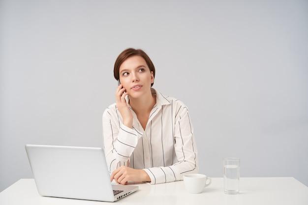 Retrato interno de uma jovem ocupada de cabelos castanhos com maquiagem natural, trabalhando em um escritório moderno com seu laptop, segurando o telefone celular e fazendo ligação enquanto posava em branco