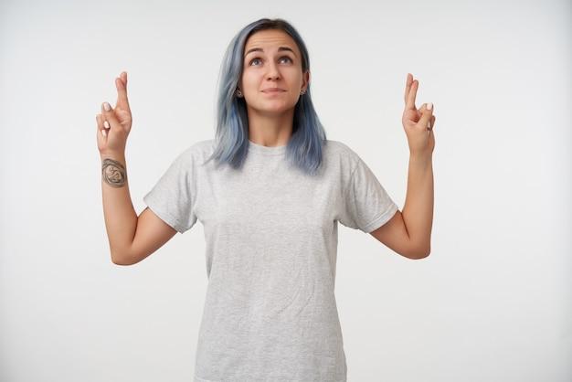 Retrato interno de uma jovem positiva tatuada com maquiagem natural, levantando as mãos com os dedos cruzados enquanto sonha com algo, isolado no branco