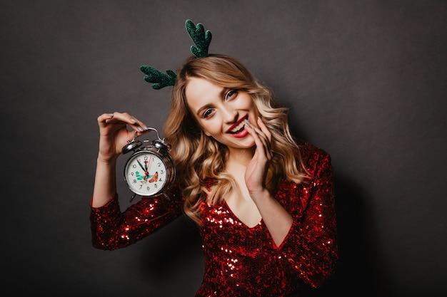 Retrato interno de uma linda mulher com relógio