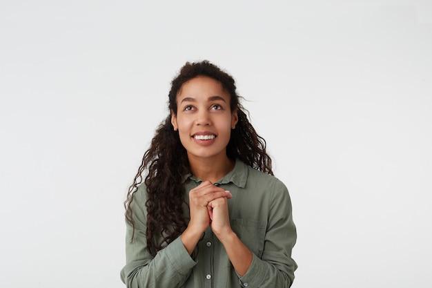 Retrato interno de uma mulher alegre, de cabelos castanhos, cabelos cacheados, pele escura e penteado casual, sorrindo amplamente enquanto olha para cima e mantendo a mão levantada junto, isolado no branco