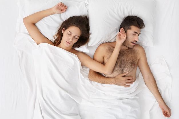 Retrato interno de uma mulher caucasiana atraente dormindo na cama, deitada em lençóis brancos, lado a lado com o marido barbudo