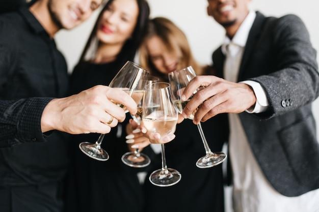 Retrato interno de uma mulher loira romântica relaxando na festa de um amigo e posando com uma taça cheia de champanhe