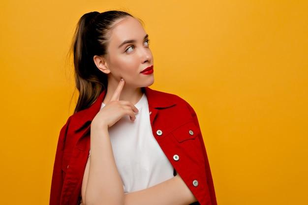 Retrato interno de uma mulher muito elegante com cabelo castanho recolhido e lábios vermelhos vestida com jaqueta vermelha e t-shirt branca poses em parede isolada, olhando para o lado com emoções concentradas