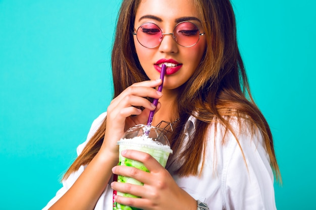 Retrato interno de uma mulher muito fofa bebendo um saboroso milk-shake verde