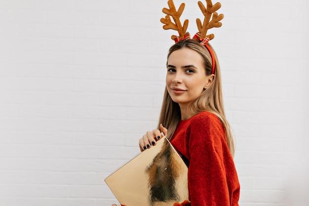 Retrato interno de uma senhora bonita e charmosa posando com um presente, vestindo uma camisola vermelha e acessórios para a cabeça sobre um fundo isolado
