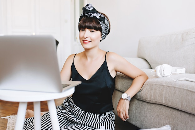 Retrato interno de uma sorridente mulher de negócios trabalhando com o computador, sentada no chão