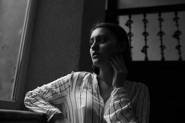 Retrato interno em preto e branco de uma jovem misteriosa e triste vestindo uma camisa branca listrada