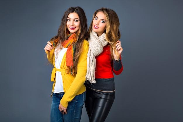 Retrato interno engraçado de garotas hipster se divertindo no estúdio, vestindo suéteres de cashmere clássicos e lenços