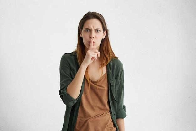 Retrato interno isolado de uma jovem européia furiosa com roupa casual, carrancuda, gesticulando com o dedo, mantendo-o nos lábios, pedindo para manter o silêncio