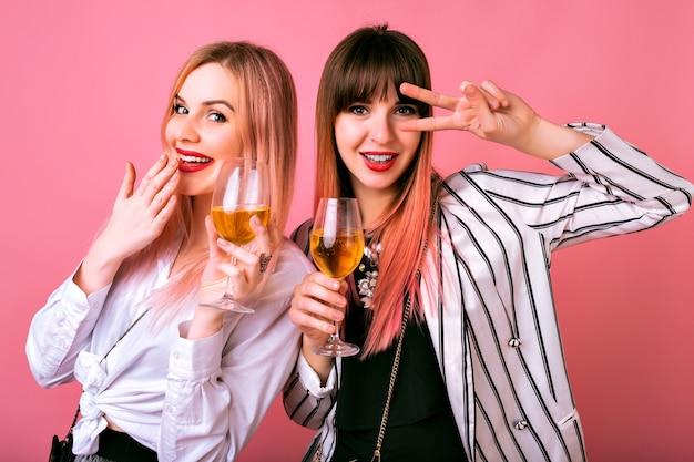 Retrato interno positivo de duas mulheres bonitas elegantes e elegantes se divertindo na festa, bebendo champanhe saboroso e dançando, roupas de noite de coquetel e parede rosa