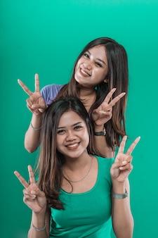 Retrato irmã gêmea mulher asiática sorrindo felicidade e dando o símbolo da paz em um fundo verde