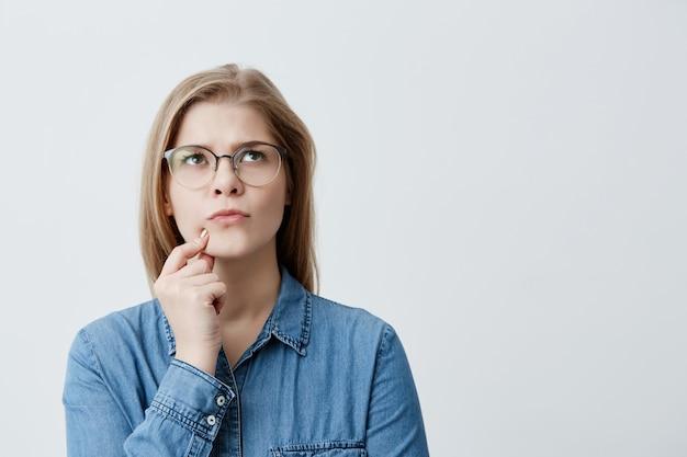 Retrato isolado da elegante jovem loira de camisa jeans e óculos, tocando o queixo e olhando de soslaio com expressão duvidosa e cética, suspeitando que o namorado dela estivesse mentindo para ela