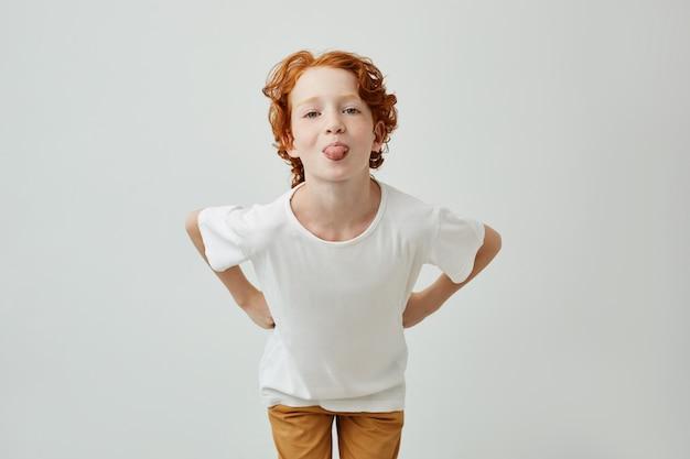 Retrato isolado de adorável menino engraçado com cabelo ruivo, segurando as mãos na cintura, se divertindo e mostrando a língua