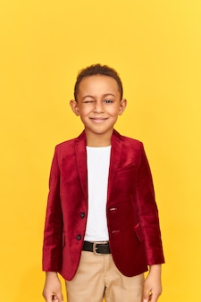 Retrato isolado de bonito rapaz de pele escura numa jaqueta de veludo, posando na parede amarela, mantendo um olho fechado.