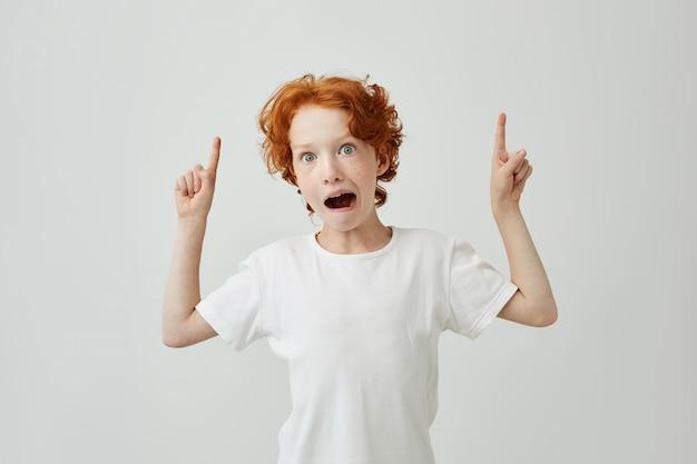 Retrato isolado de engraçado menino ruivo com sardas tendo surpreendido olhar com a boca aberta, apontando um lado com as duas mãos.