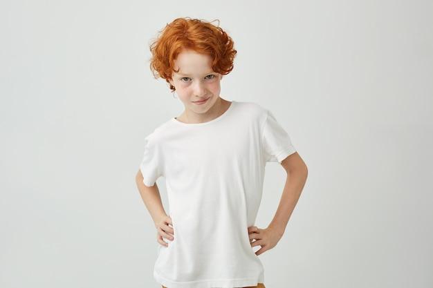 Retrato isolado de engraçado menino ruivo na camiseta branca, segurando as mãos na cintura