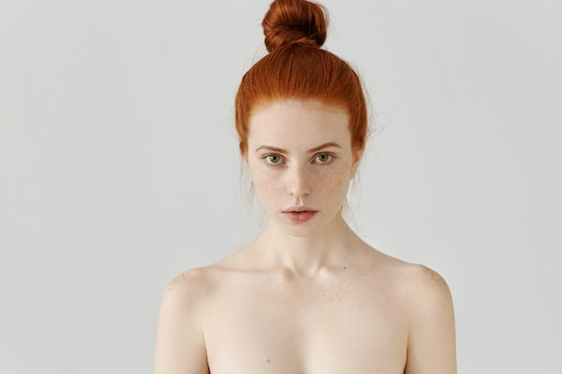 Retrato isolado de mulher jovem e bonita ruiva caucasiana com coque de cabelo e pele limpa perfeita com sardas em pé na parede cinza com os ombros nus