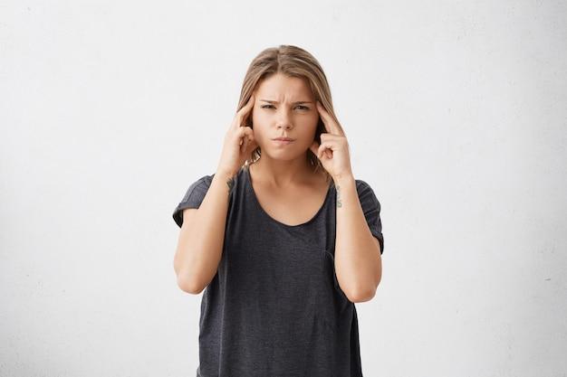 Retrato isolado de mulher jovem mestiça, estressada e frustrada, vestida com uma camiseta casual escura, segurando os dedos nas têmporas como se estivesse tentando se lembrar de algo muito importante.