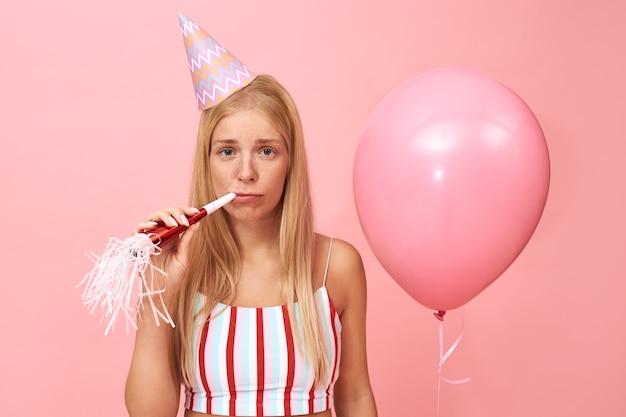 Retrato isolado de triste triste jovem europeu feminino usando chapéu cônico e top de verão comemorando aniversário, tendo expressão facial chateada soprando chifre de festa