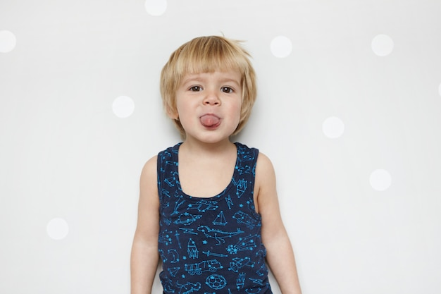 Retrato isolado de um adorável menino engraçado com olhos azuis, vestindo uma camiseta regata, se divertindo dentro de casa, mostrando a língua, provocando, encostado na parede com espaço para cópia